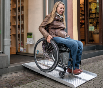 Roll·stuhl·fahrerin auf mobiler Rampe
