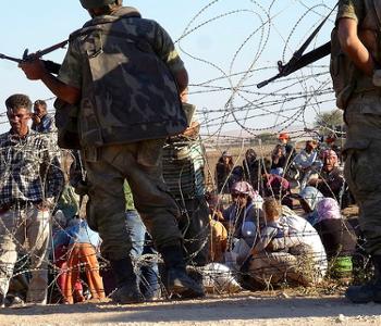 Zaun und Soldaten an der Grenze