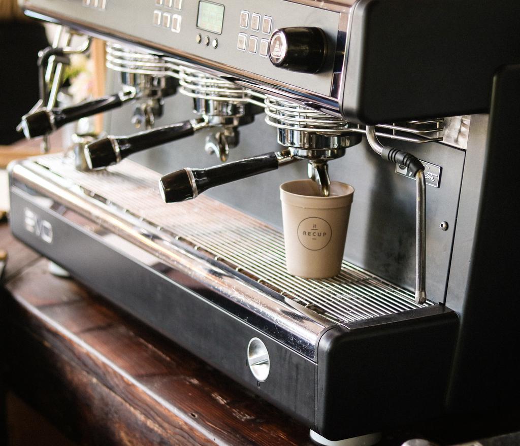 Mehrwegbecher und Kaffeemaschine