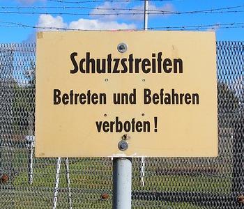 Schild an der Grenze mit der Aufschrift: Schutzstreifen. Betreten und befahren verboten.