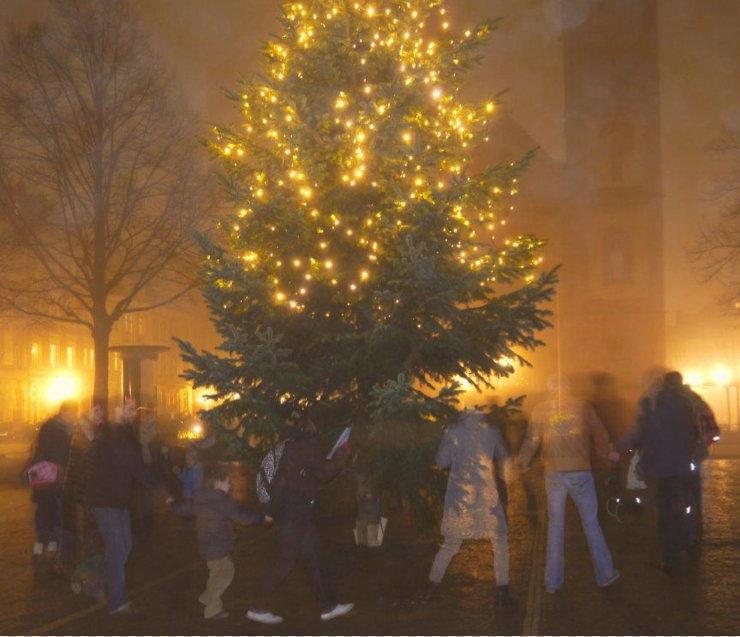 Menschen um Weihnachtsbaum
