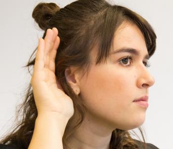 Eine Frau hört mit der Hand am Ohr