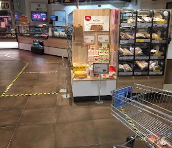 Das Foto zeigt einen Einkaufswagen im Supermarkt. Auf dem Boden sind Linien. Di Menschen sollen Abstand halten und an den Linien stehen bleiben. Zum Beispiel beim Anstehen an der Kasse.