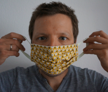 Ein Mann zieht eine Maske aus