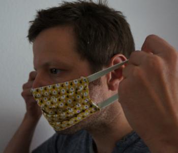 Ein Mann zieht eine Maske an
