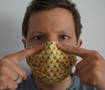 Ein Mann hat eine Maske an. Er zeigt auf den Rand der Maske.