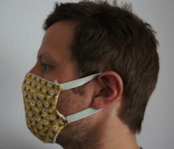 Ein Mann hat eine Maske an. Man sieht den Mann von der Seite