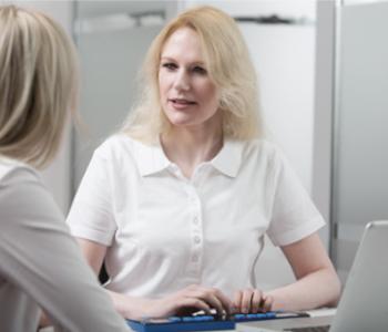 Frau an der Braille·zeile und im Gespräch
